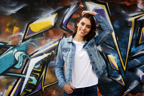 Pretty young woman in blank t-shirt against graffiti wall