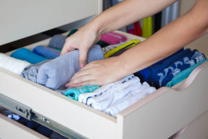 woman folding t shirts in drawer