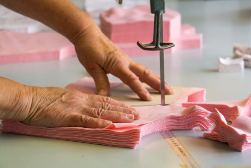 woman cutting several layers of fabric