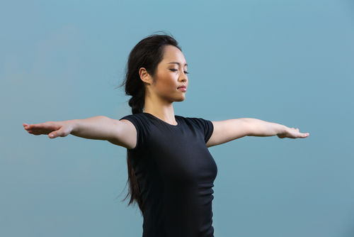 woman standing meditating in a yoga pose