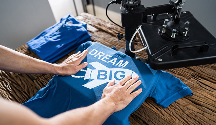Man Printing On T Shirt In Workshop
