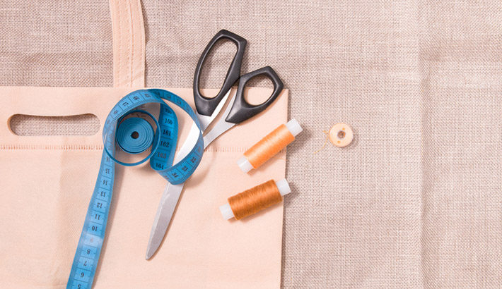 bag, scissors, measuring tape and several spools of thread